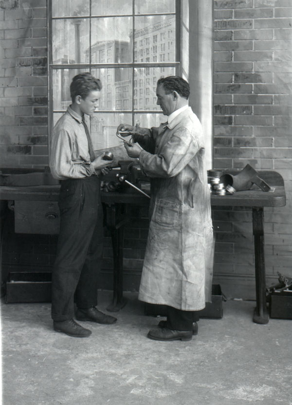 vintage blue collar apprentice learning from mentor in workshop