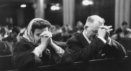 vintage couple praying in church pew kneeling