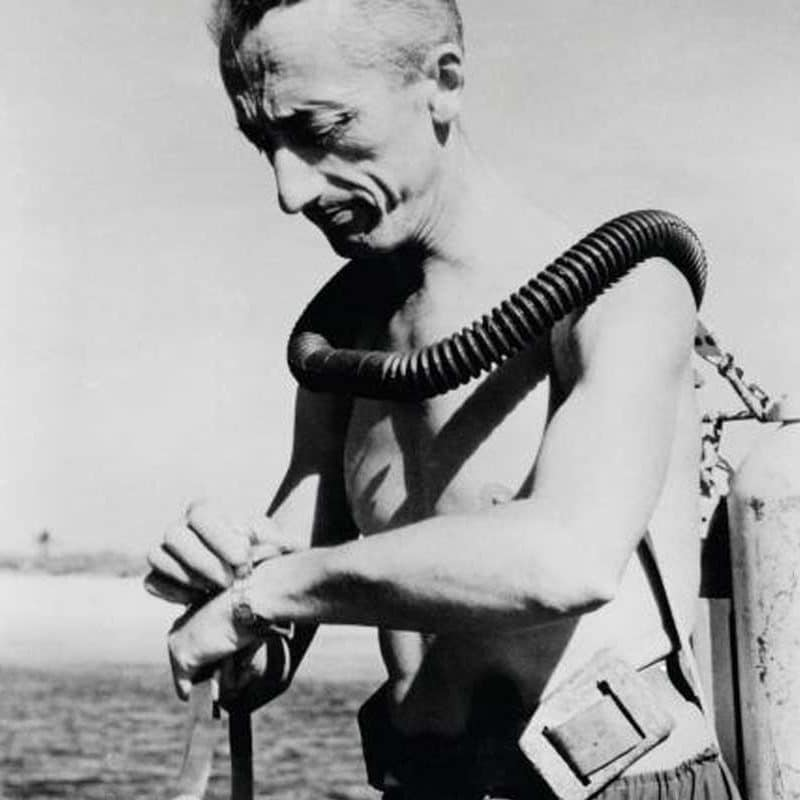 Vintage Jean Jacques Cousteau getting ready to dive into water.