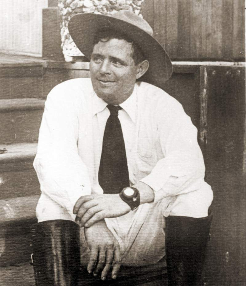 Jack London sitting on porch wearing pocket watch wristlet.
