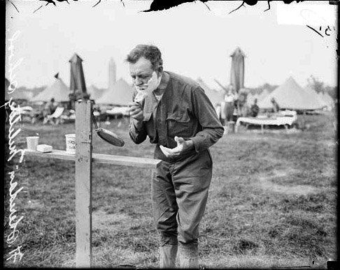 Vintage soldier shaving with brush at outside.