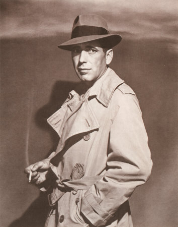 Humphrey bogart wearing fedora and trench coat cigarette in hand.