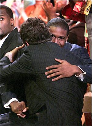 Men shaking hand while giving hug.
