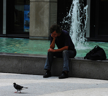 Man sitting on fountain ledge bird is next to him.