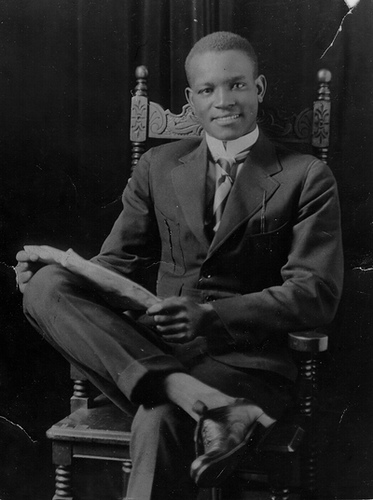 Vintage African American man in chair looking at camera.