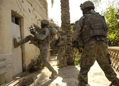 Soldier kicking down door to open.