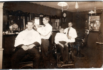 Vintage men getting haircuts in barber shop.