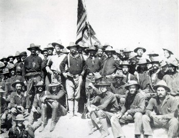 Theodore Roosevelt standing with rough riders.