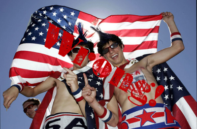 Soccer fans holding american flag drapped over them.