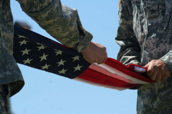 Two soldiers folding an American flag.