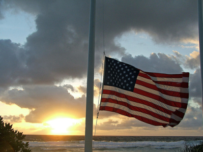 American flag in front of ocean sunset.