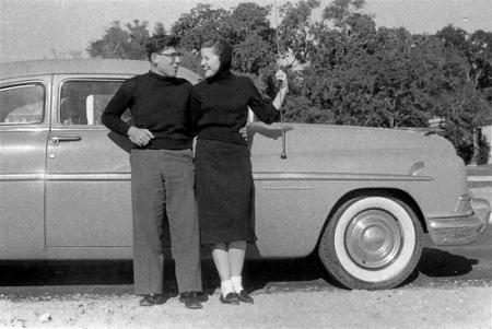 vintage 1950s couple standing in front of car