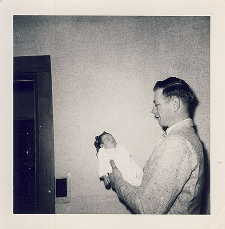 Vintage father holding newborn in room.
