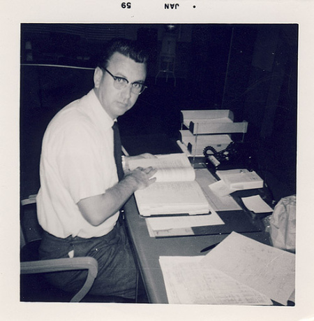 Vintage man sitting at desk with a textbook.