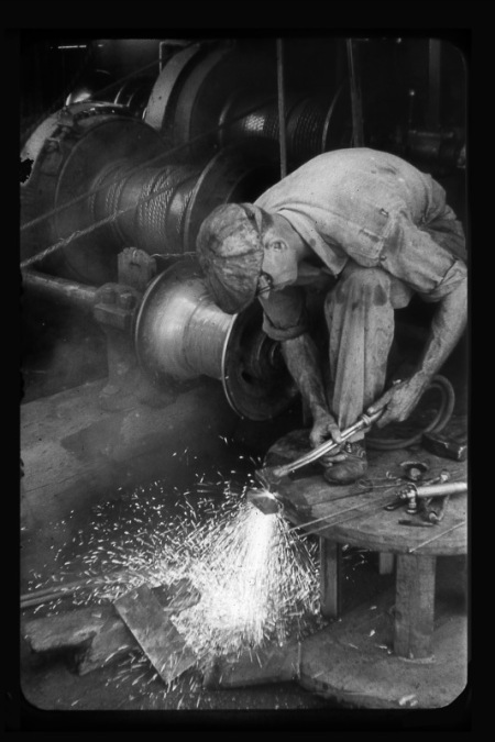 Vintage man welding in factory.