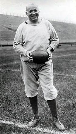 Vintage Knute Rockne standing in football ground.