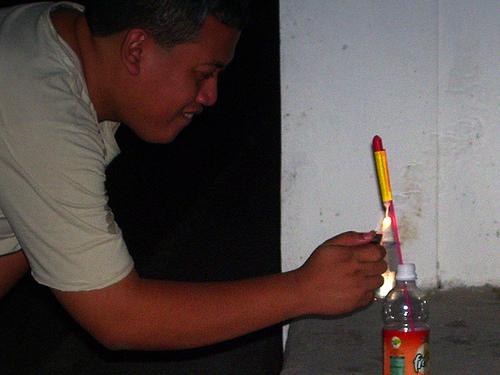 Man lighting bottle rocket firework.