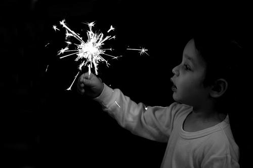 Child lightening a sparkler fireworks.
