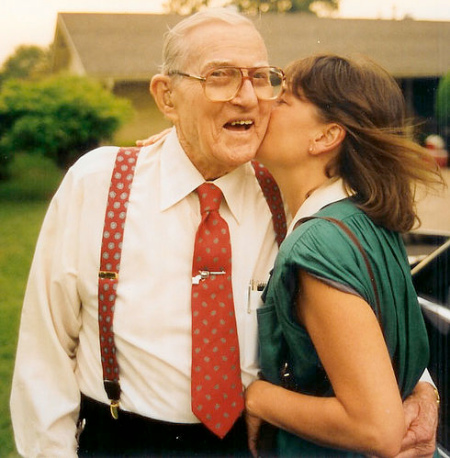 elderly man wearing tie bar being kissed by young woman