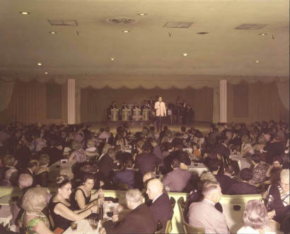 Bob Hope doing comedy in public hall.