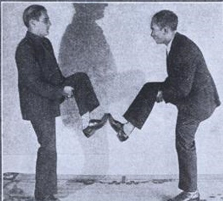 Vintage men foot boxing early.