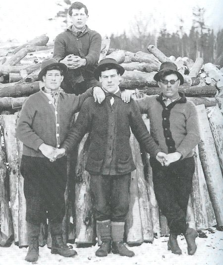 Vintage group of male friends standing and one sitting on the log.