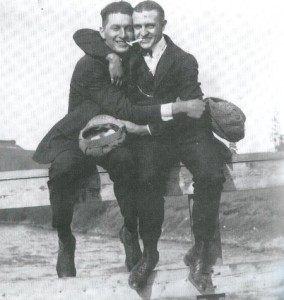 Vintage mens sitting and both having hands on each other.