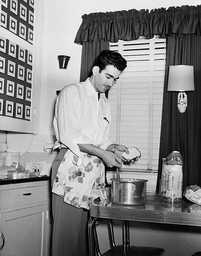 vintage 1940s man with apron cooking in kitchen