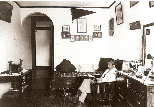 Vintage man reading in dorm room.