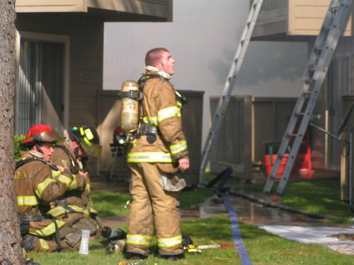fireman on the job looking at burning house