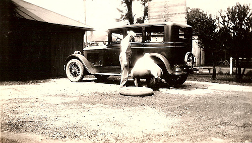 vintage men changing flat tire 1920s