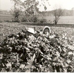 Vintage kids enjoying in leaf pile.