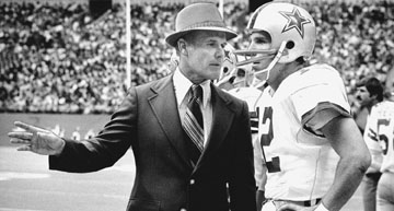 Vintage Tom Landry giving instructions to football player in ground.