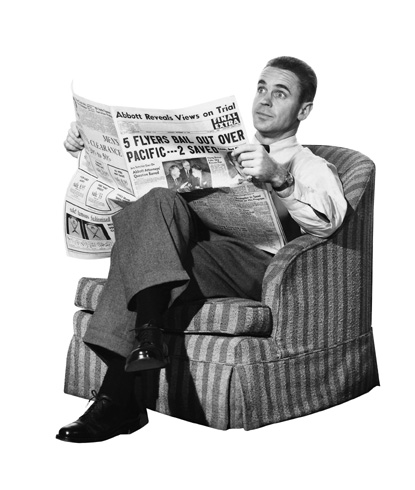 Vintage man sitting on chair and reading newspaper.