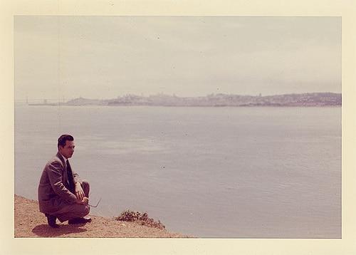 vintage man in suit kneeling near water 1960s