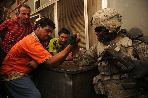 A man doing arm wrestling with soldier.