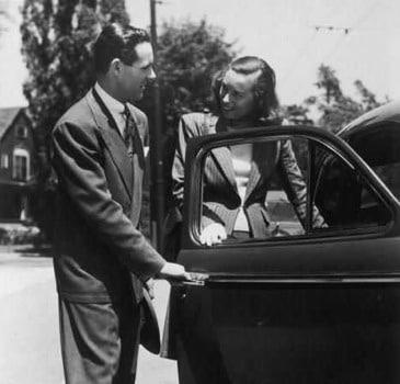 vintage man opening car door for woman 1950s