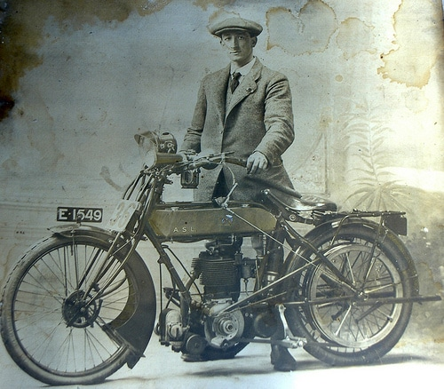 vintage man next to motorbike motorcycle early 1900s