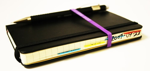 Moleskin notebook and pen fitted with ribbon.