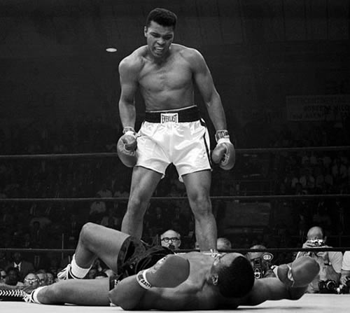 Muhammad Ali stands over Sonny Liston in boxing ring.