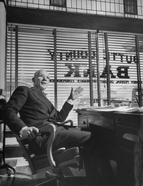 Vintage banker sitting on the chair in his office.