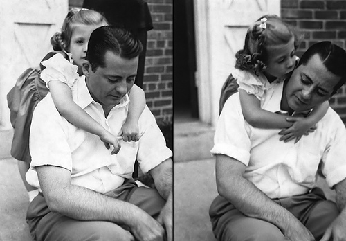 Vintage little daughter hugging and kissing her father.