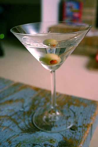 Martini cocktail in the glass with olives.