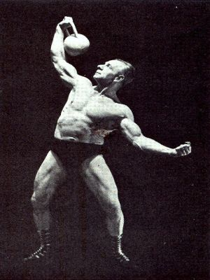 Man carrying kettlebell with one hand.