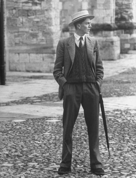 Vintage gentleman with umbrella standing on the road.