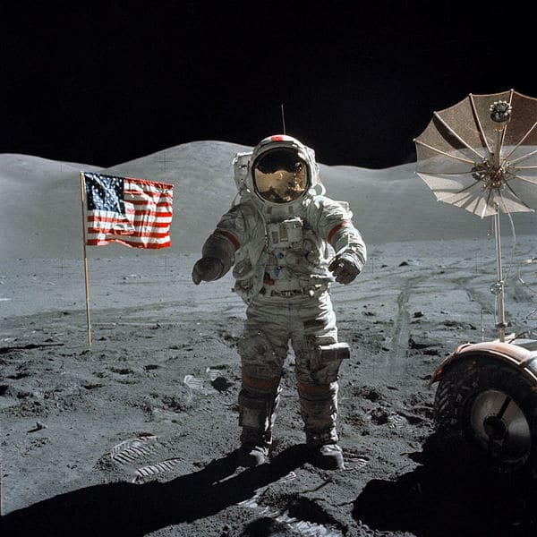 A Astronaut standing on a moon with American flag and flash on back.