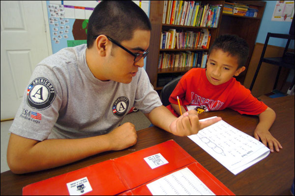 Americorps employee working with young student.
