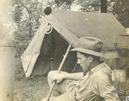 Vintage man lying outside the tent and holding stick.