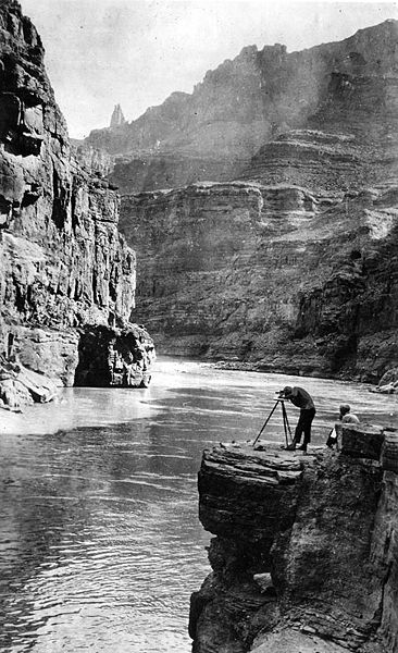 Man standing on a rock of Colorado River with camera stand.