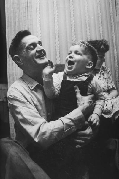 Vintage father playing with toddler son.